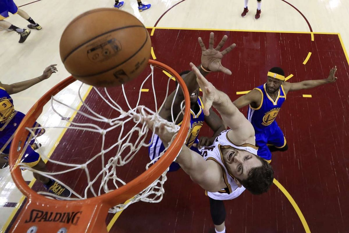 Cleveland Cavaliers forward Kevin Love (C) goes to the basket as Golden State Warriors forward Draymond Green (L) and Golden State Warriors guard Ian Clark (R) defend in the second half of the NBA Finals basketball game three between the Golden State
