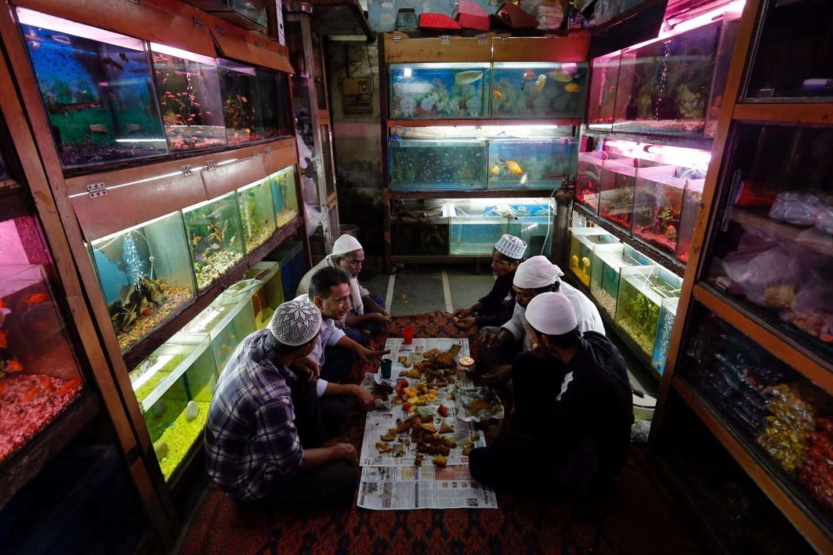 Muslims eat their Iftar (breaking fast) meals inside a shop selling fish during the holy month of Ramadan, in Mumbai, India, June 7, 2017. PHOTO: REUTERS