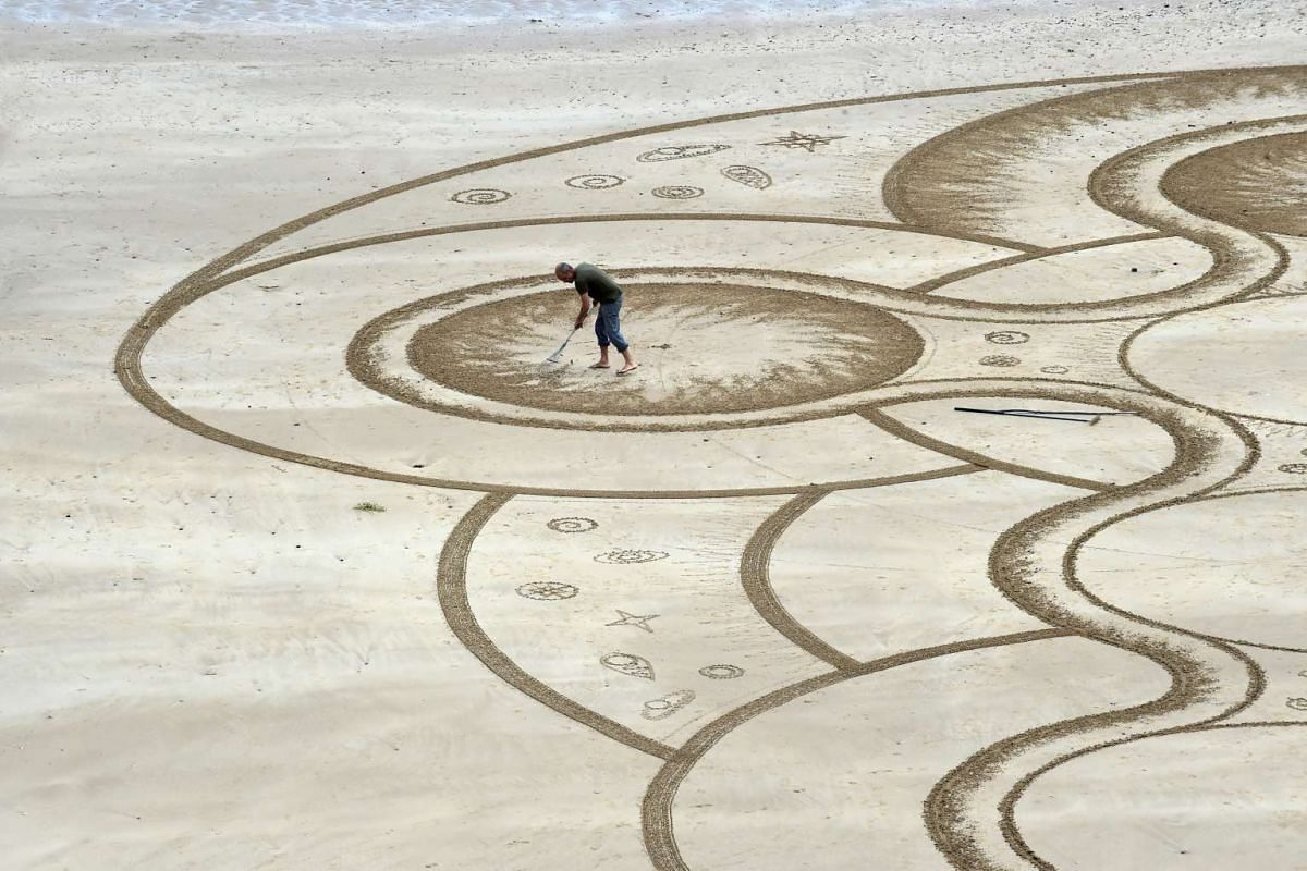 Sand artist Marc Treanor creates a work on the North Beach at Tenby Harbour, Pembrokeshire, Wales, Britain June 7, 2017. PHOTO/REUTERS
