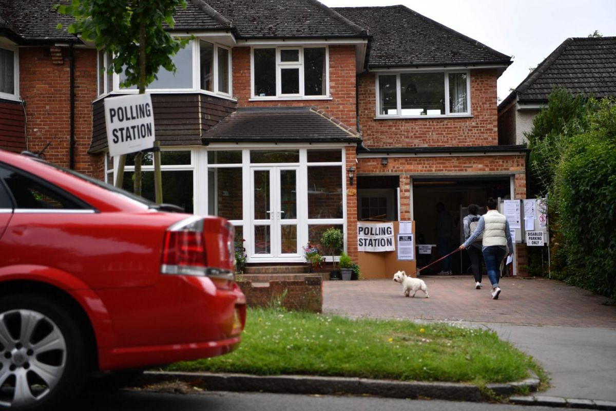 Voters arriving at a polling station set up in the garage of a private residence in Croydon, south London, on June 8, 2017.