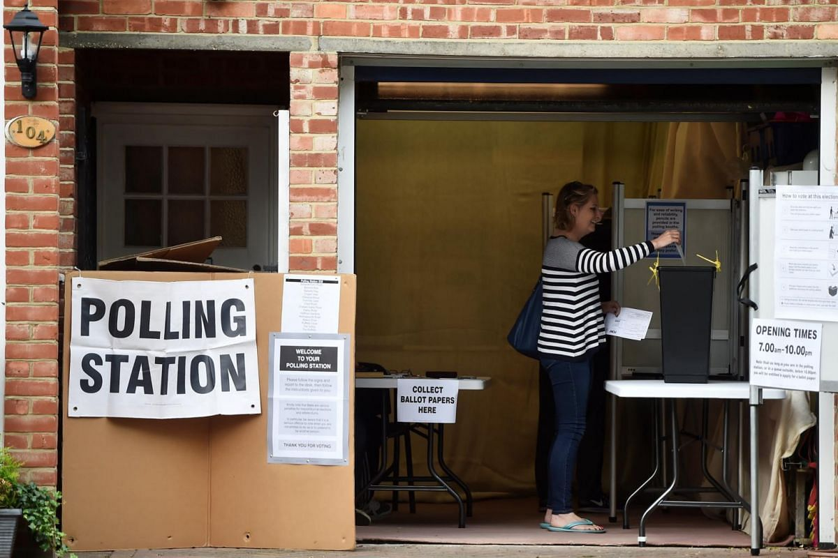 A woman casting her ballot at a garage which is being used as a polling station in Croydon, south London, Britain, on June 8, 2017.