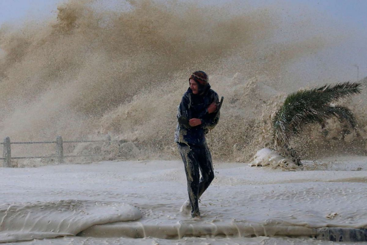 A man runs from sea spray as storms hit Cape Town, South Africa on June 7, 2017.