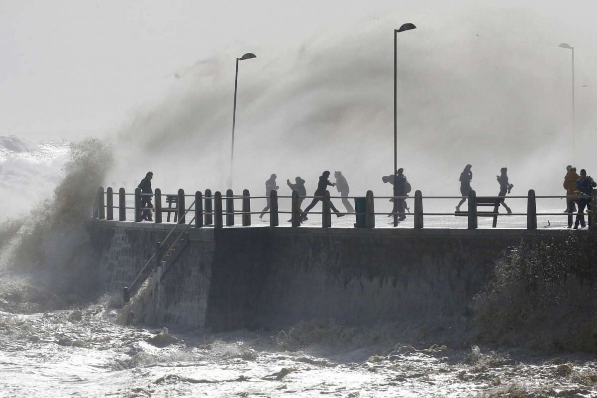 People run from sea spray as storms hit Cape Town, South Africa on June 7, 2017.