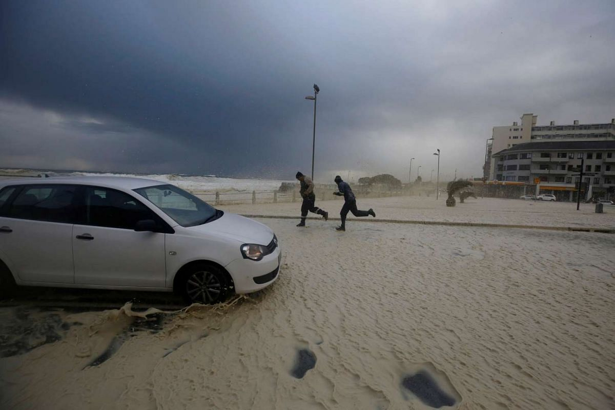 People running away from sea spray as storms hit Cape Town, South Africa on June 7, 2017.