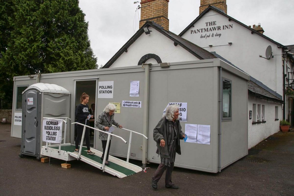 People are pictured outside a polling station in Cardiff, Wales, on June 8, 2017.
