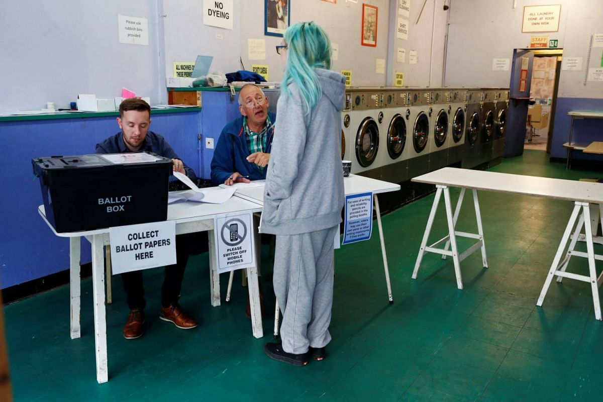 A woman voting at a launderette used as a temporary polling station in Oxford, England, on June 8, 2017.