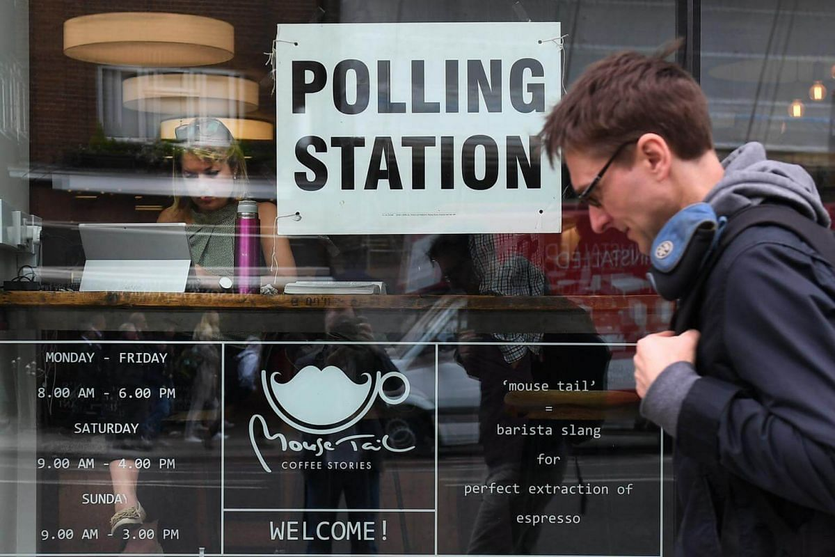 A man passing a coffee shop on Borough High Street serving as a polling station for the British General election in London, on June 8, 2017.