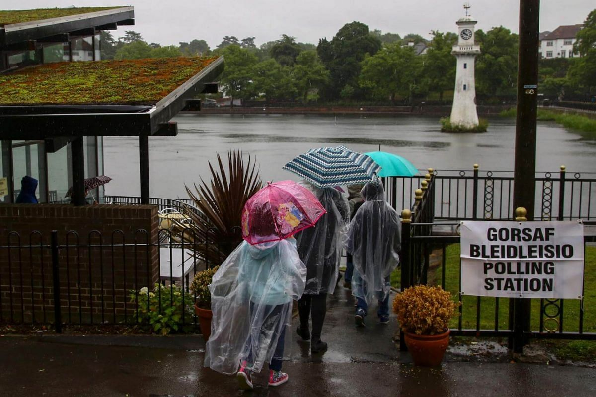 People are pictured outside a polling station at Roath Park Lake in Cardiff, Wales, on June 8, 2017.