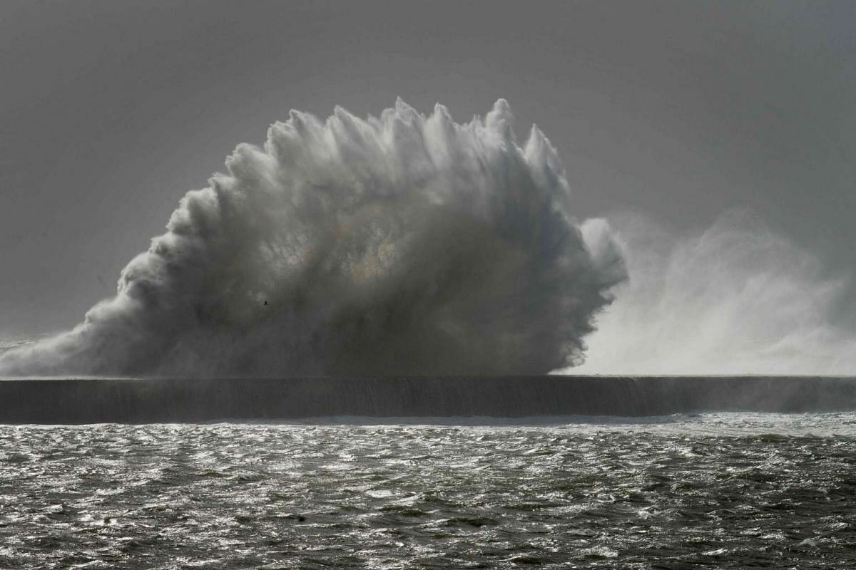 Waves break over a sea wall at Cape Town harbour as an intense storm hits South Africa's west coast on June 7, 2017.