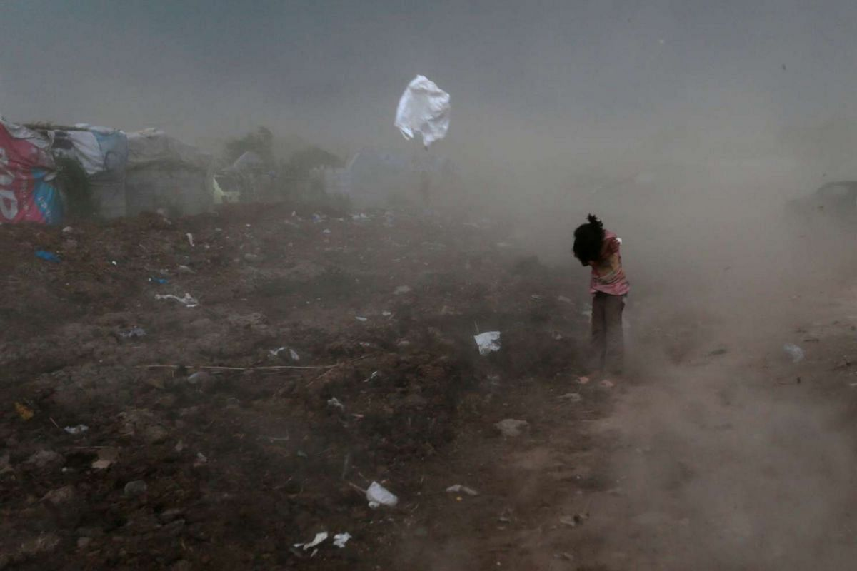 A girl protects herself from garbage and dust, raised by a gust of wind, in a slum in Islamabad, Pakistan June 8, 2017. PHOTO: REUTERS