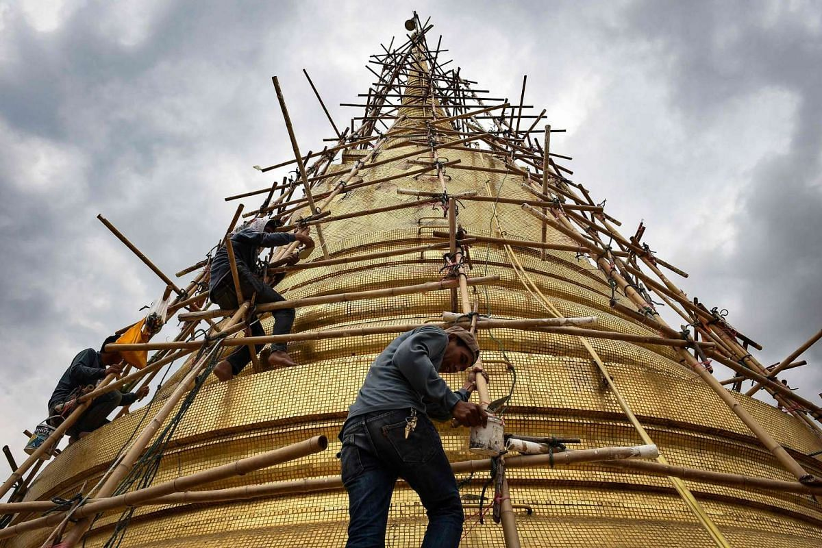 Workers repair the gold tiles on the chedi atop of Wat Saket Buddhist temple, in Bangkok on June 8, 2016. PHOTO: AFP