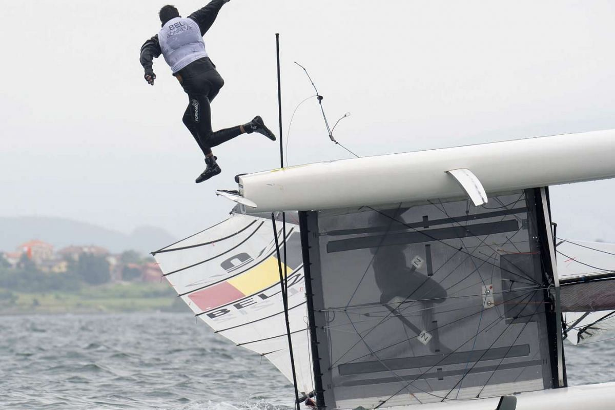 Belgian yatchman Kevin Bonnevie (L) jumps after overturning his ship in the Nacra category during the Sailing World Cup final held in Santander, Spain, on June 8, 2017. PHOTO: EPA