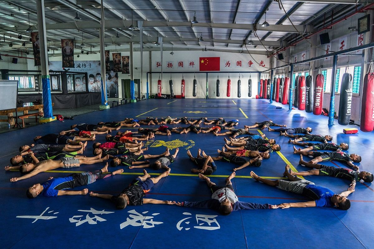 Groups of students lie on the mats before warming-up for the morning training session, on May 26, 2017.