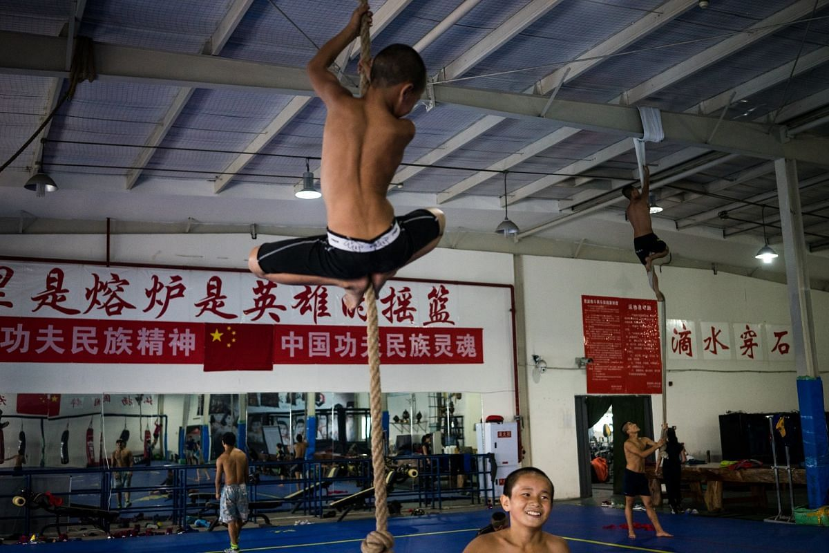 Students climb a rope after the morning group training, on May 24, 2017.