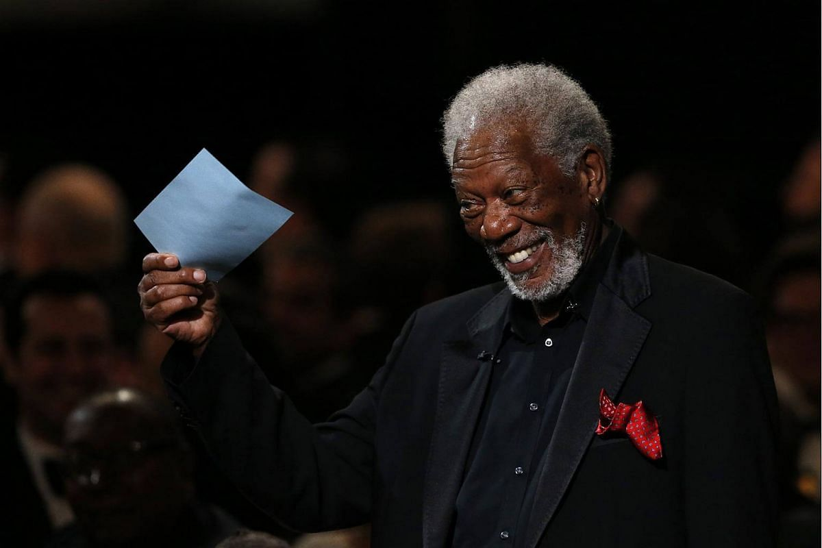Actor Morgan Freeman holding a note card while on stage.