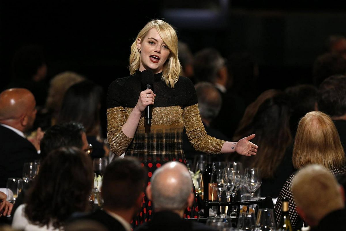 Actress Emma Stone speaking amid show attendees.