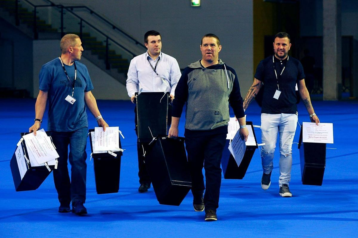 Staff members carrying the first ballot boxes as they arrive at the main Glasgow counting centre in Emirates Arena in Glasgow, Scotland, on June 8, 2017.