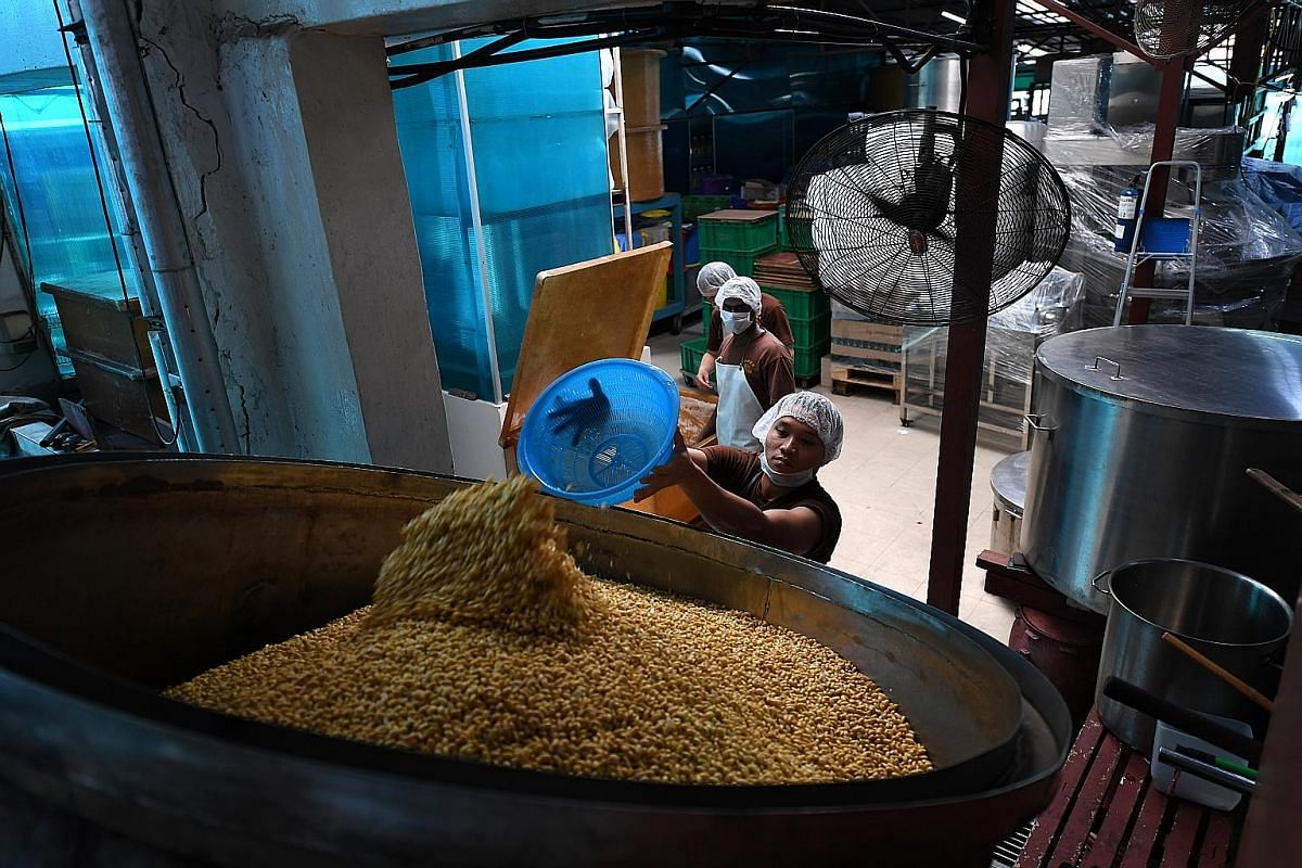 After four to seven days of fermentation indoors, the soya beans are transferred to baskets to be taken to the vats of brine in the courtyard where the fermentation process will continue under the sun. Ms Hannah Woo and factory worker Saw Lae Ka Lae