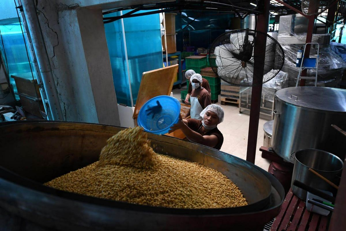 A worker transfers soaked beans to a steaming tank for steaming.