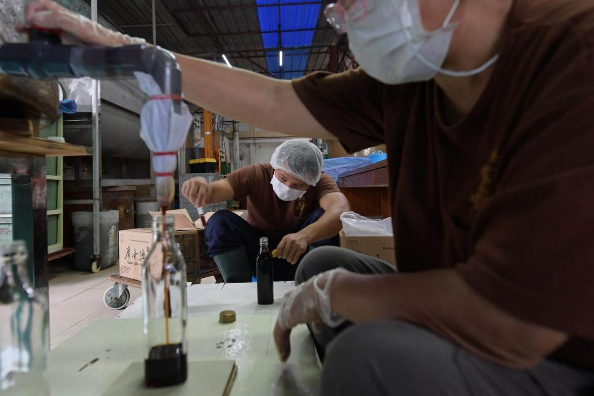 Hannah Woo filters the company's premium range of soya sauce into bottles while a worker adjusts the amount of soya sauce in each bottle with a syringe.