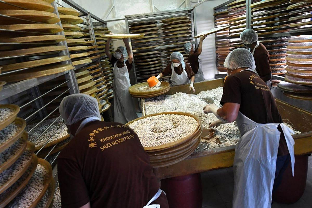 Director of Kwong Woh Hing, Simon Woo (bottom, left), Simon's sister, Hannah Woo (third from left) and their workers placing coated soya beans onto trays.