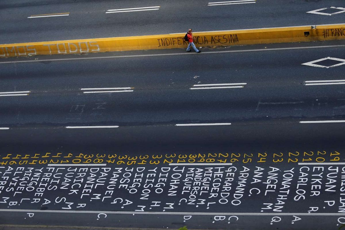 A pedestrian walks past a list of the victims of the violence during protests against Venezuela's president Nicolas Maduro government in Caracas, Venezuela, June 12, 2017.