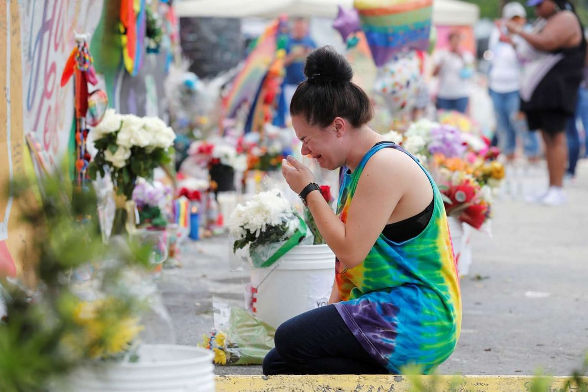 Chelsea Nylen reacts while visiting the memorial outside the Pulse Nightclub on the one-year anniversary of the shooting in Orlando, Florida, U.S., June 12, 2017.