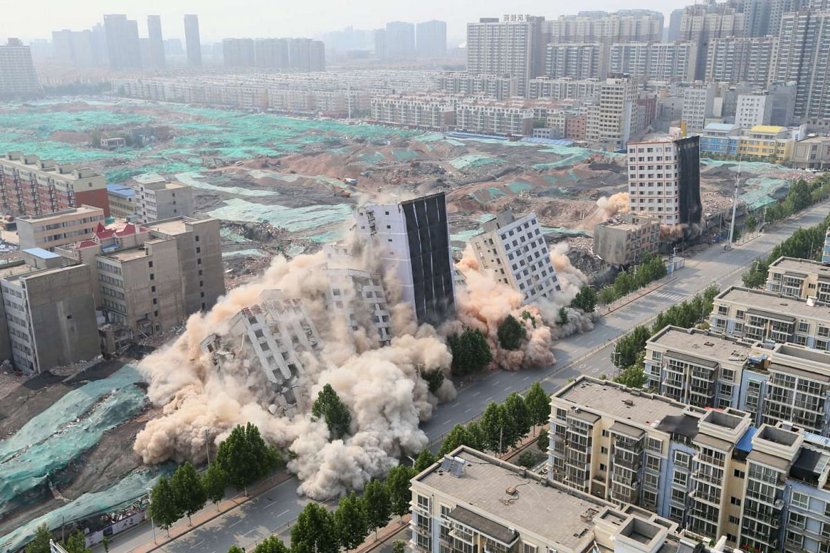 Buildings crumble during a controlled demolition for the reconstruction of urban villages in Zhengzhou, Henan province, China June 12, 2017. Picture taken June 12, 2017.