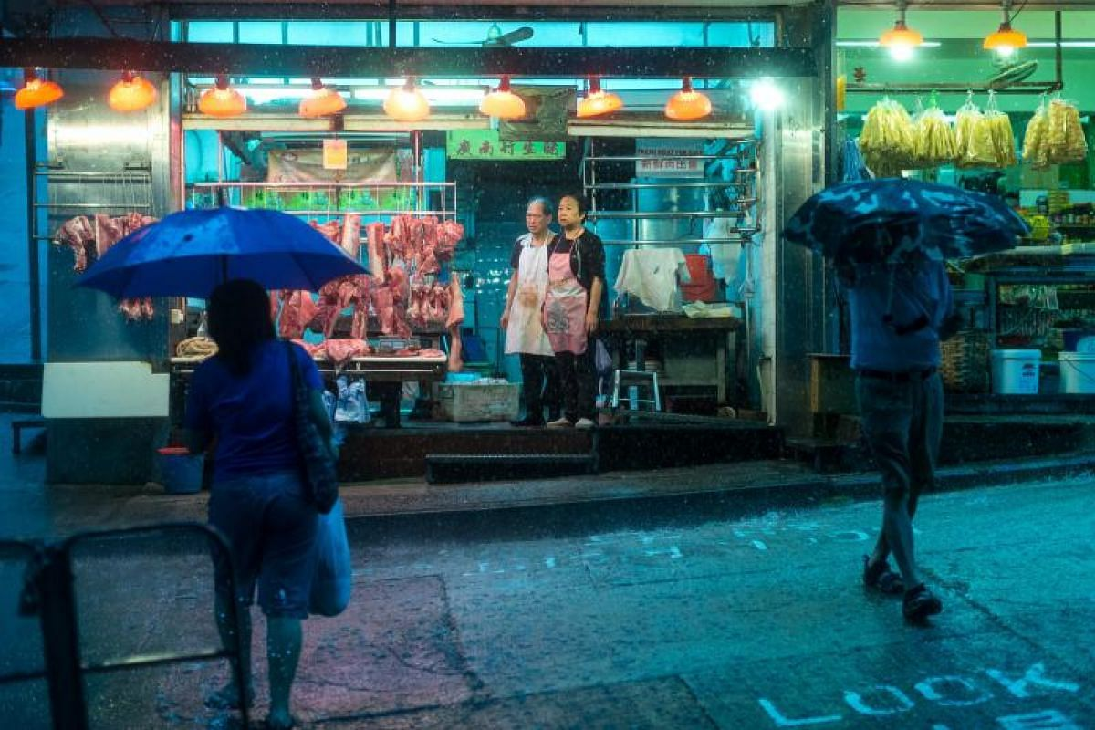 Butchers looking on during heavy rain brought by tropical storm Merbok in Hong Kong, China, on Tuesday (June 13).