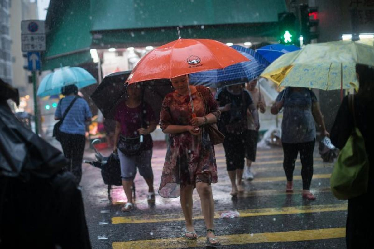 Commuters and morning shoppers holding umbrellas during torrential rain brought by tropical storm Merbok in Hong Kong, China, on Tuesday (June 13).
