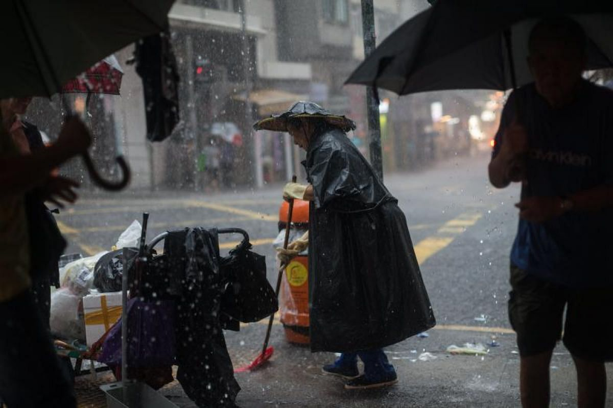 A worker sweeping a street during torrential rain brought by tropical storm Merbok in Hong Kong, China, on Tuesday (June 13).