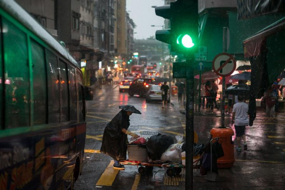 A worker collecting garbage during torrential rain brought by tropical storm Merbok in Hong Kong, China, on Tuesday (June 13).
