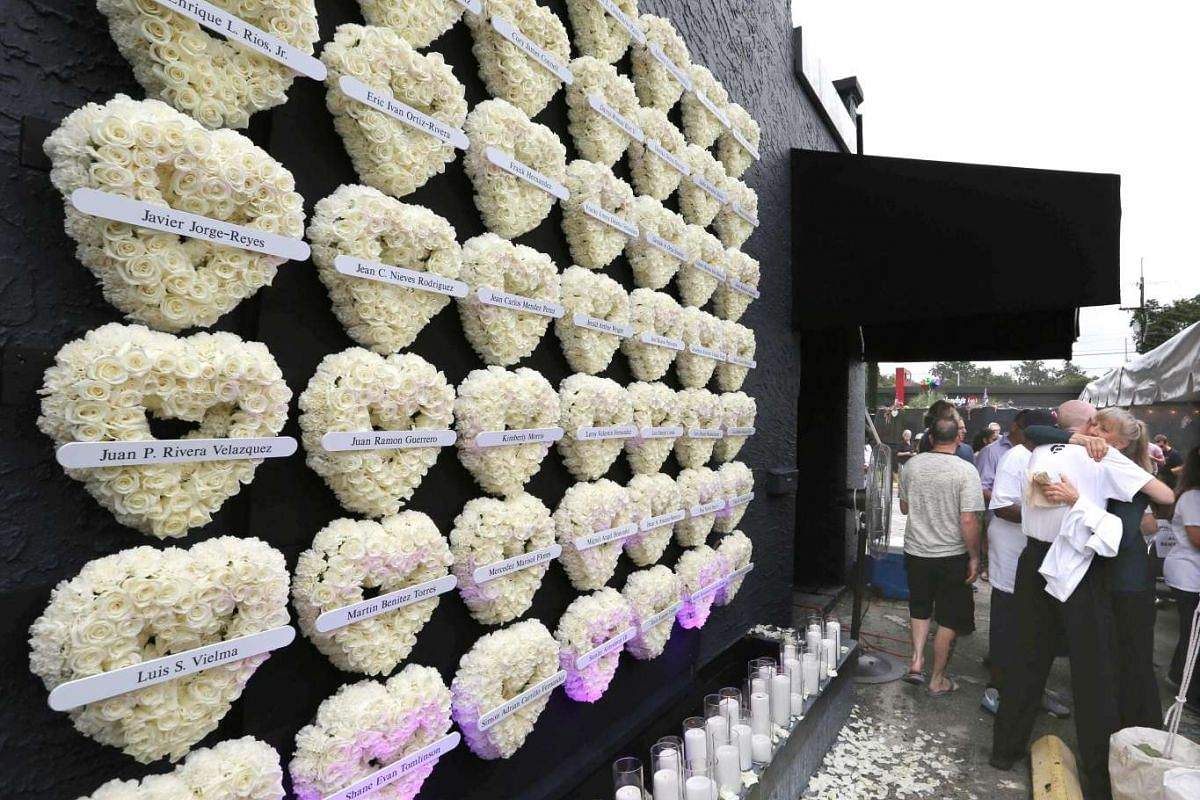 Heart-shaped floral wreaths with the names of the mass shooting vicitms adorn a wall of the Pulse nightclub during a memorial in Orlando, Florida on June 12, 2017. Orlando marked the first anniversary of the Pulse nightclub shooting that left 49 dead