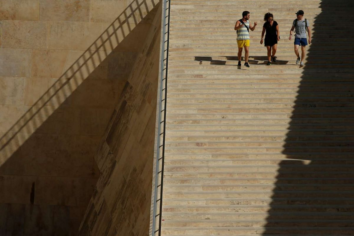 People walk down the staircase at the entrance to Valletta towards the bus terminus, outside the city walls of Valletta, Malta, June 13, 2017.