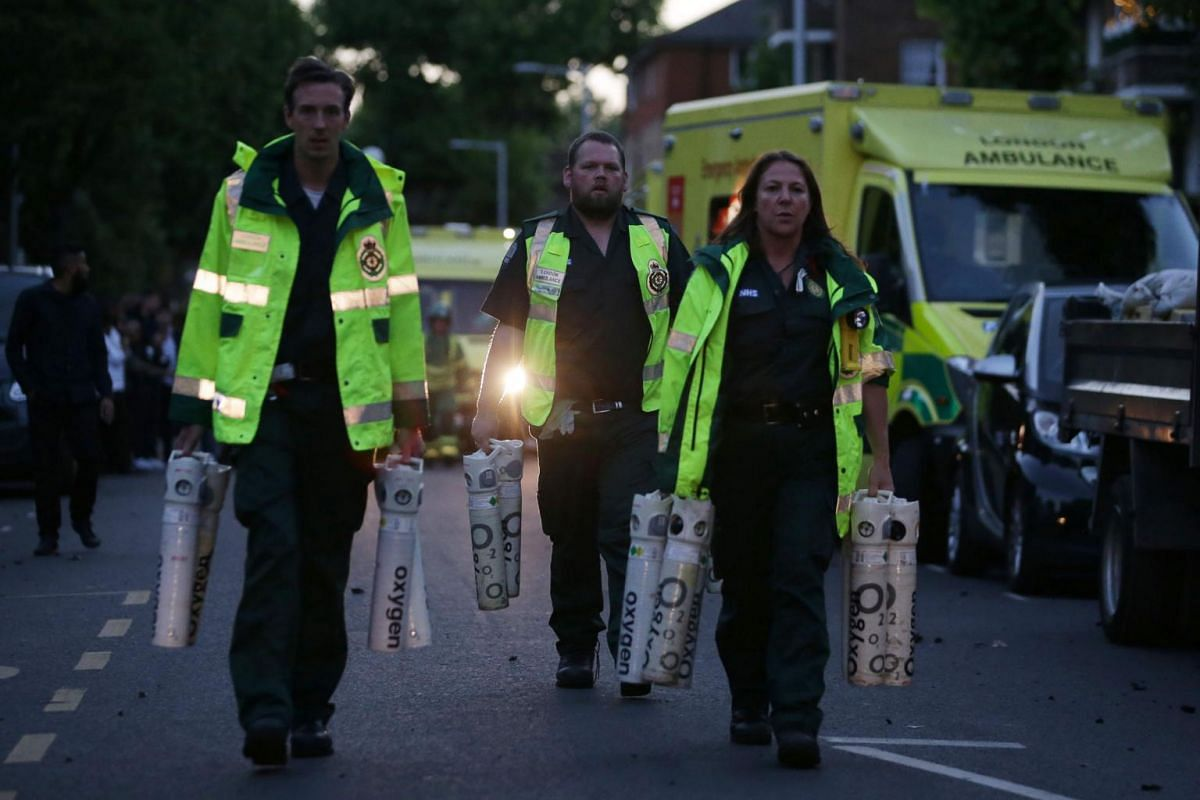 Members of the emergency services carry oxygen tanks as a huge blaze engulfs Grenfell Tower, a residential tower block on June 14, 2017 in west London.