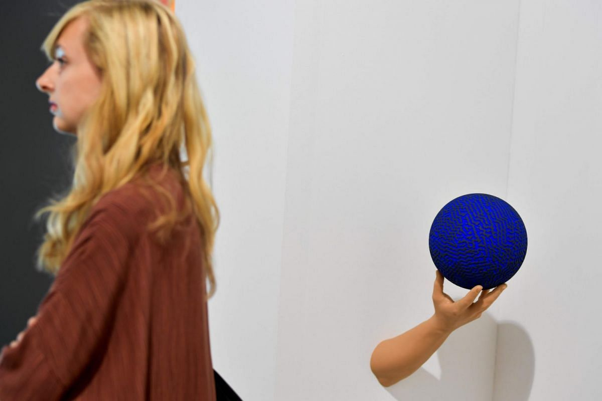 A woman walks past Untitled by Dutch artist David Nuur displayed at Pland B gallery during the preview day of Art Basel the world's premier modern and contemporary art fair on June 13, 2017 in Basel.