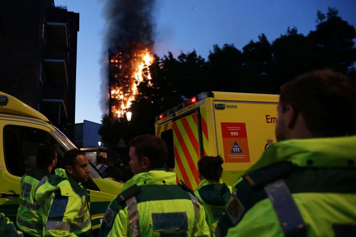 Members of the emergency services watch as Grenfell Tower is engulfed by fire on June 14, 2017 in west London.