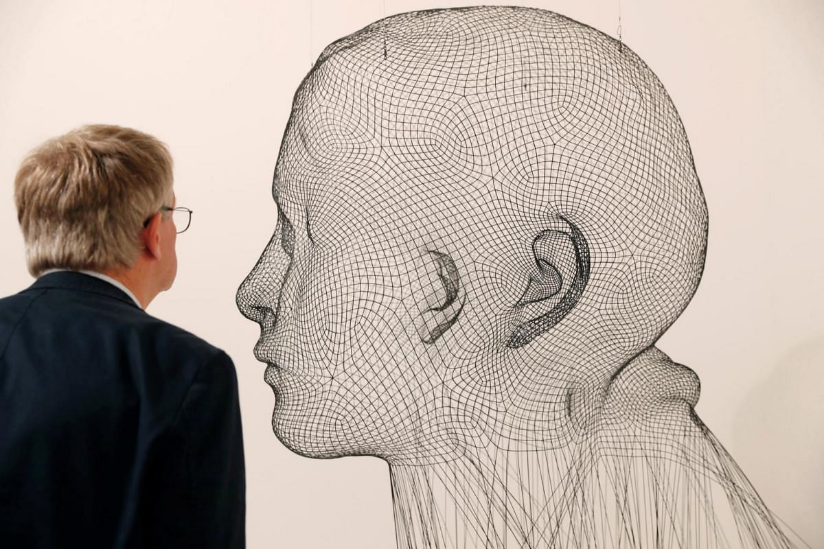 A man observes Invisible Laura from 2016 by Spanish artist Jaume Plensa during the Art Basel, Switzerland on June 13, 2017.
