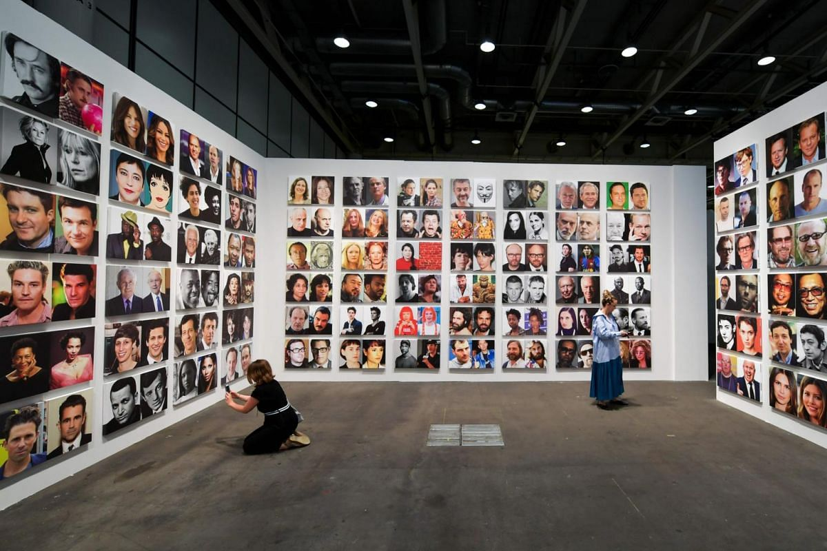Visitors discover Rob Pruitt's Official Art World / Celebrity Look-alikes Series by US conceptual artist Rob Pruitt at Unlimited show during the preview day of Art Basel, the world's premier modern and contemporary art fair, on June 13, 2017 in Bas