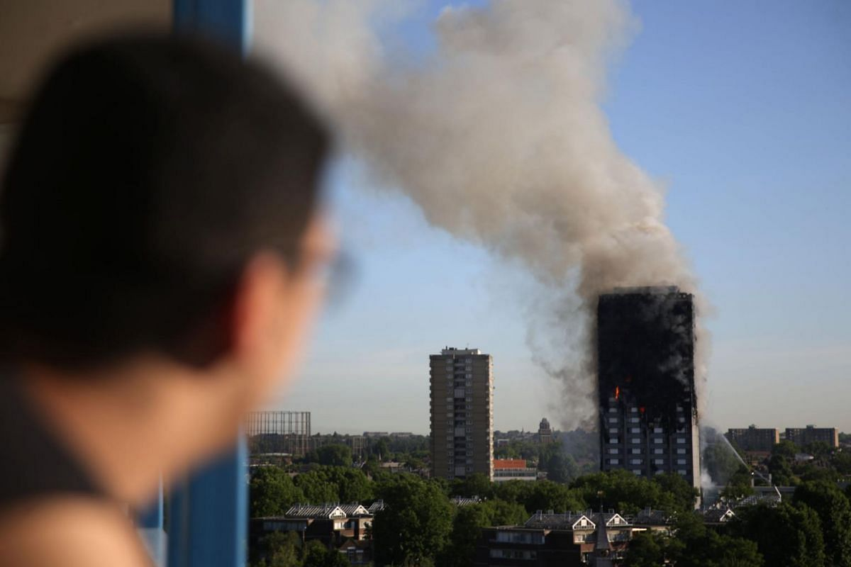 A resident of a nearby council estate watches smoke billowing from Grenfell Tower on June 14, 2017 in west London.