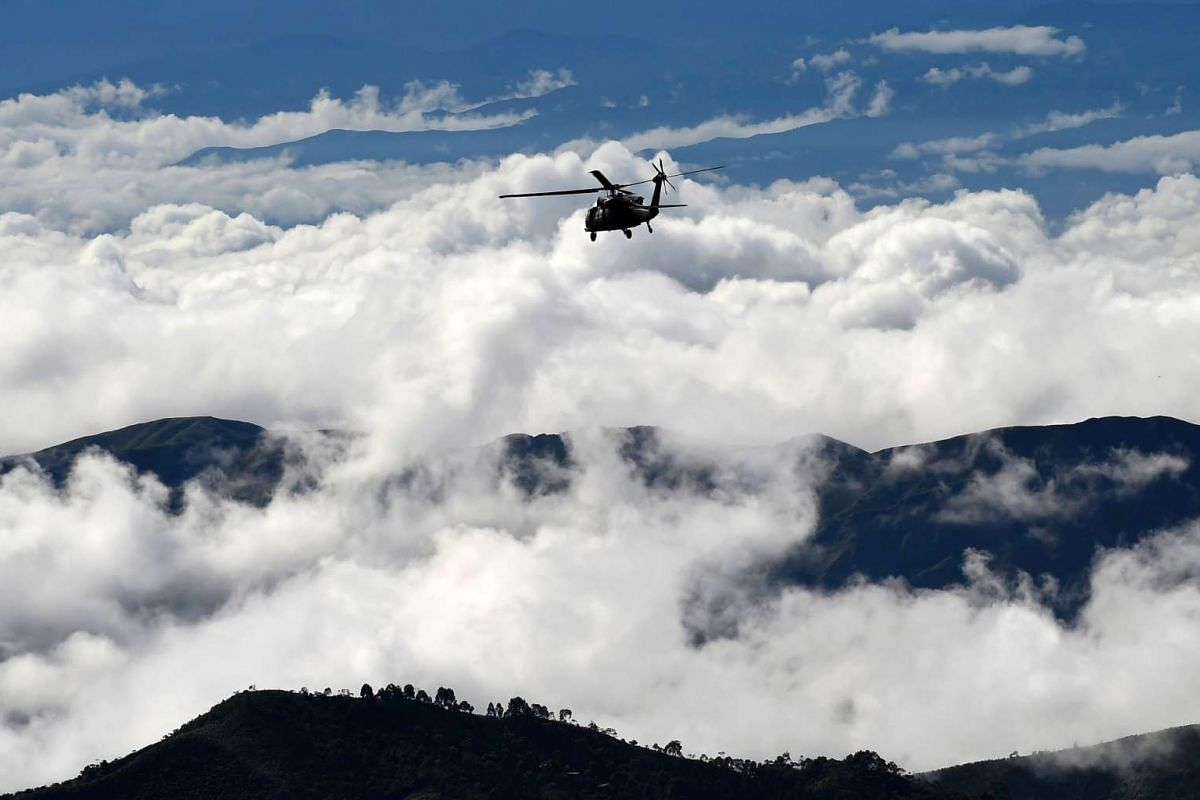 A helicoper of the Colombian army flies over a FARC demobilization zone before a ceremony as part of the peace process in Buenos Aires, Cauca Department, Colombia on June 13, 2017.
