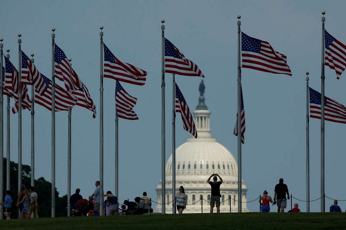 Flags fly at the Washington Monument, as the U.S. Capitol is seen at rear, on Flag Day in Washington, U.S., June 14, 2017.