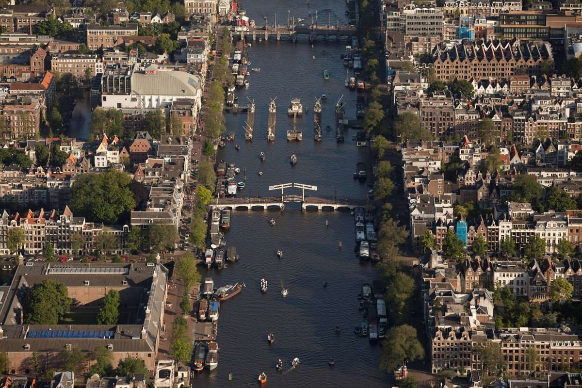 The  Magere Brug or Skinny Bridge over the Amstel river in Amsterdam, with houseboats docked on its banks.