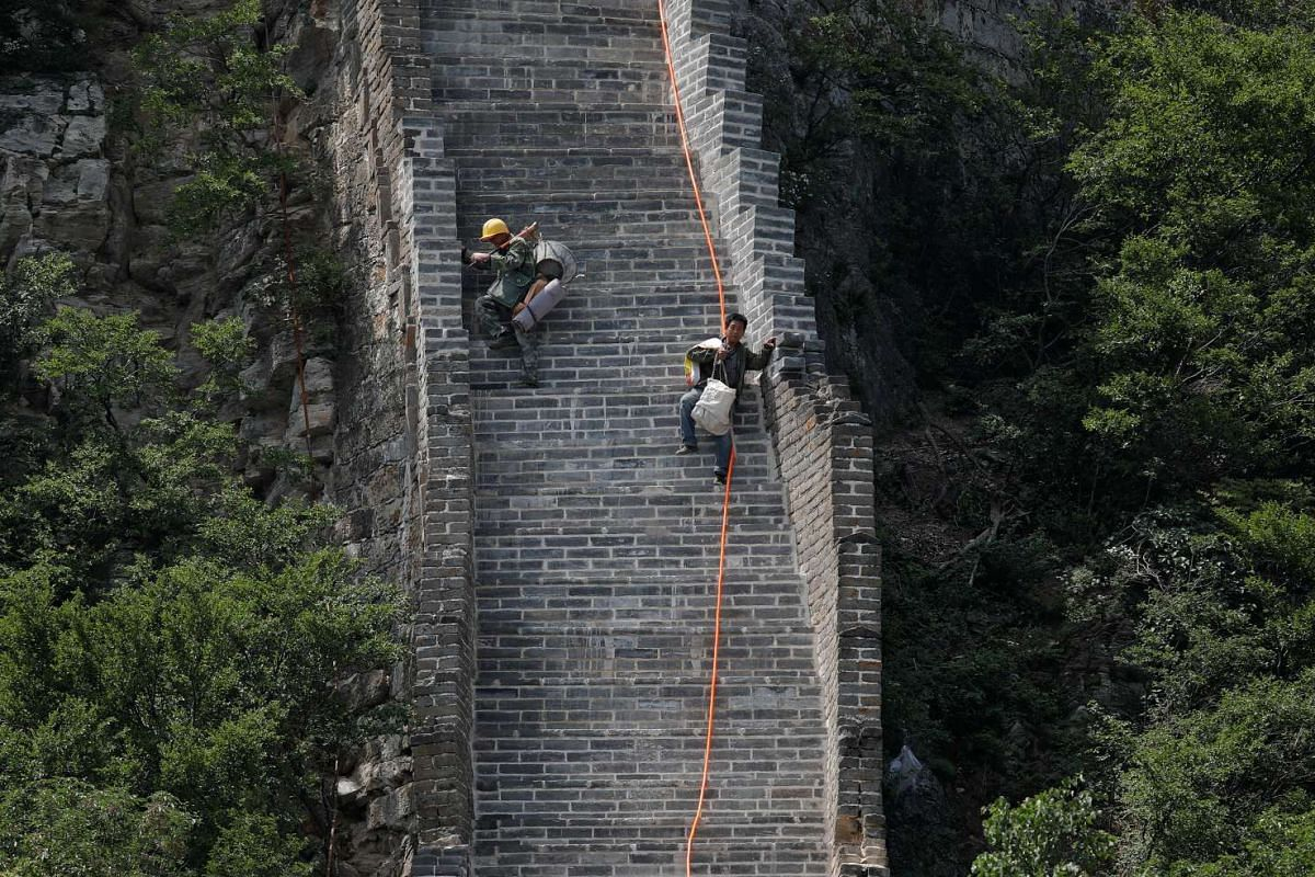 It's the end of a long and tiring day as workers carry their tools and belongings and climb down the steep steps.