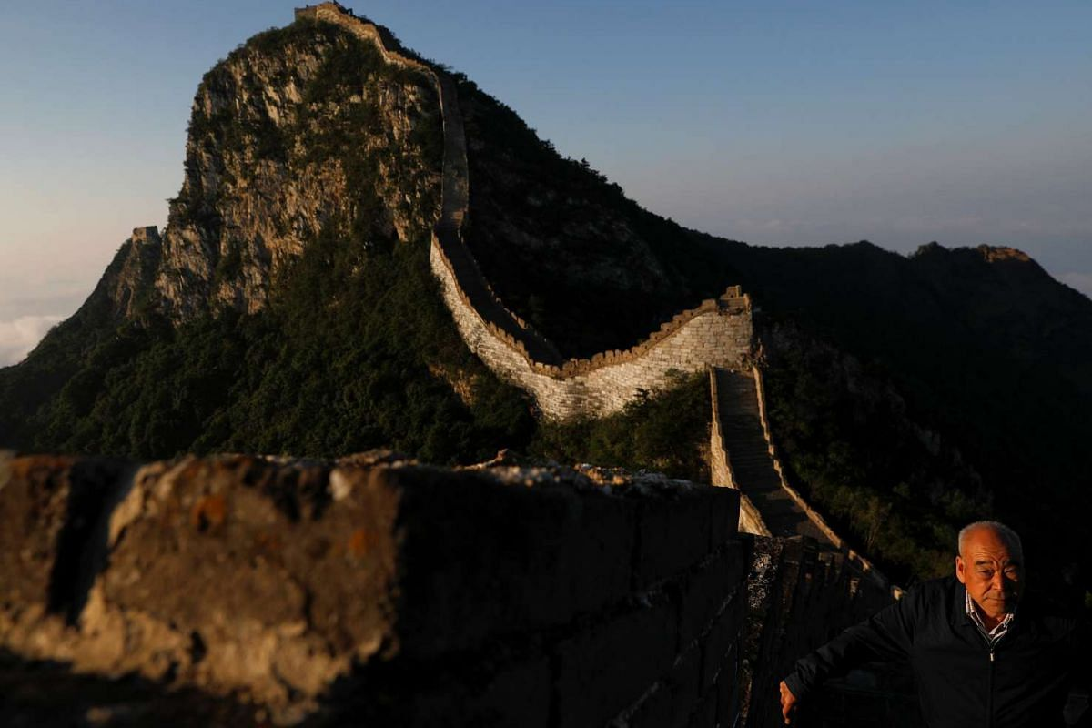 Cheng Yongmao, the engineer in charge of the reconstruction project on the Jiankou section of the Great Wall, surveying the scene on June 7 as the sun rises behind him.