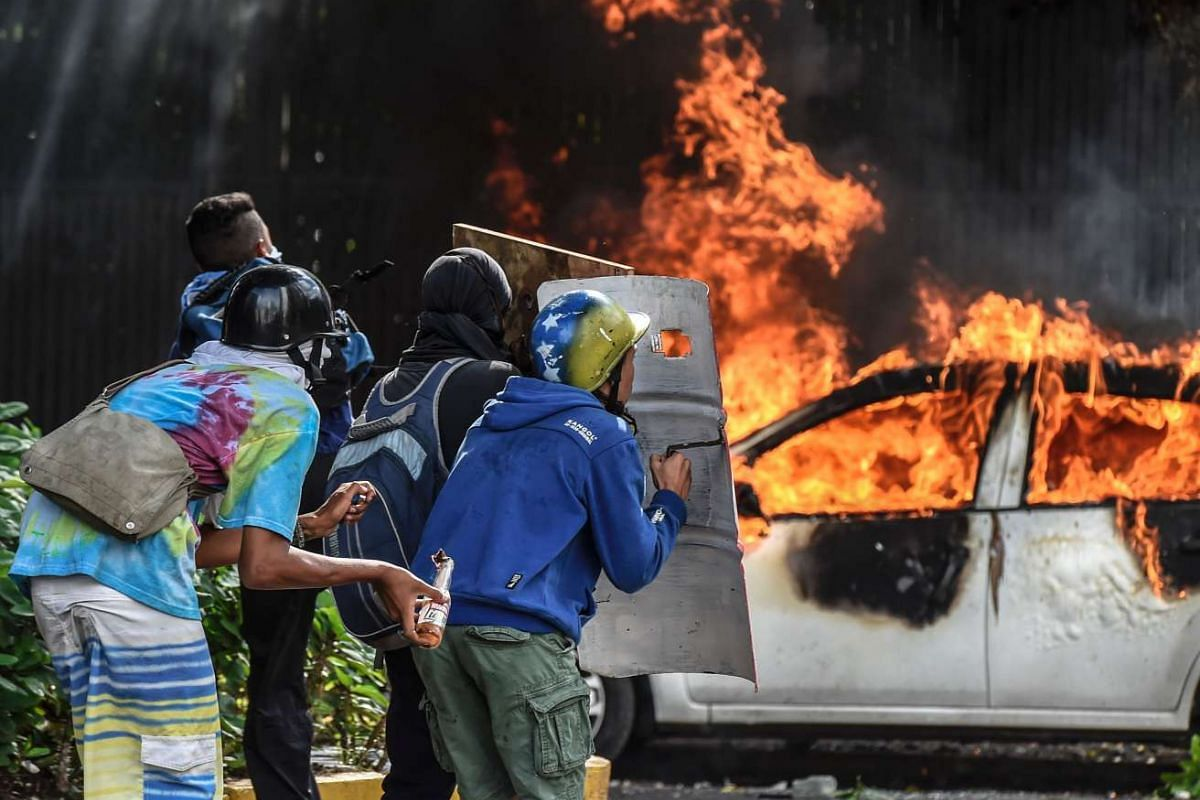 Anti-government demonstrators take cover behind shields near a burning car during clashes near Altamira Square in Caracas, on June 14, 2017.