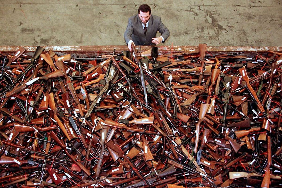 Mick Roelandts, firearms reform project manager for the New South Wales Police, looks at a pile of around 4,500 prohibited firearms that have been handed in over the past month under the Australian government's buy-back scheme in Sydney, Australia.