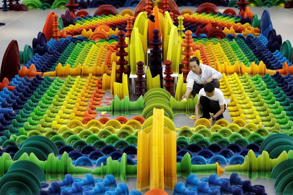 "Chinese artist Li Hongbo (front) and his assistant set up his work ""Ocean of Flowers"" at Eight One Art Museum in Beijing, China June 14, 2017. According to Li, nearly 2000 sculptures in shape of different weapons, made of hundreds of pieces of bright"