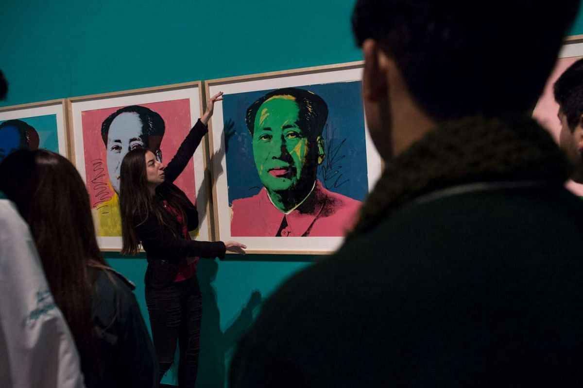 People look at 'Mao' a work by US artist Andy Warhol depicting former Chinese leader Mao Zedong, during an exhibition of the legendary pop artist at the La Moneda Museum in Santiago, June 15, 2017.