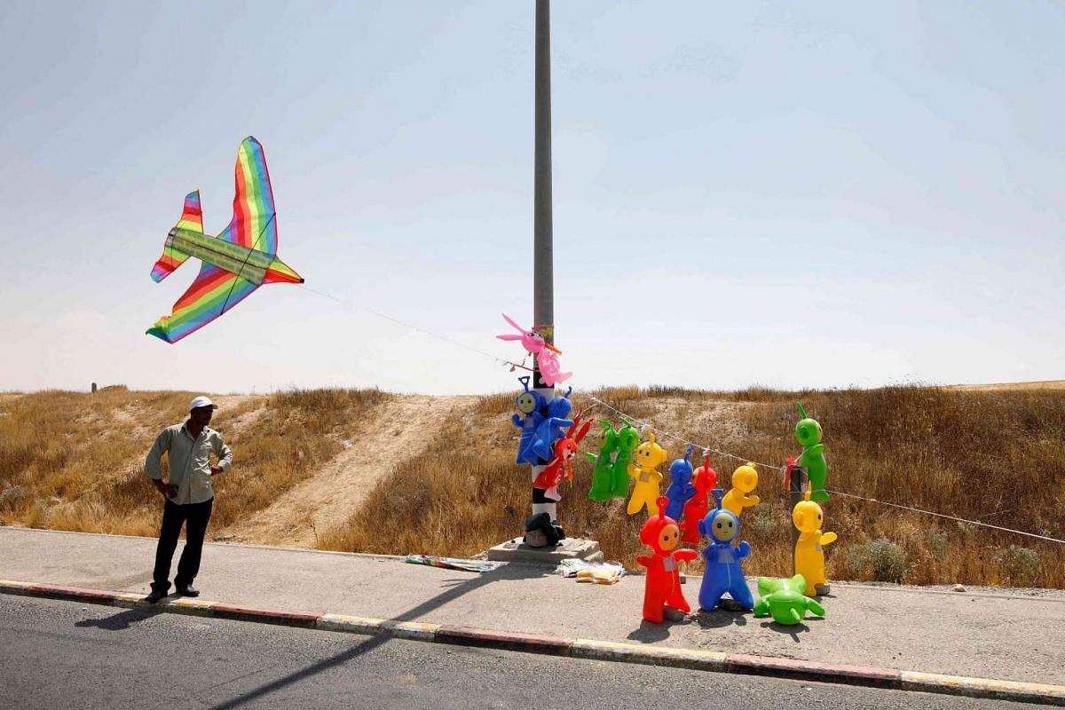 A street vendor sells balloon puppets on the highway near the southern Bedouin city of Rahat on June 15, 2017.